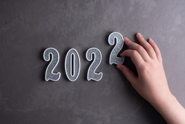 Una mano femminile mette un numero d'argento 2 nel 2022 su uno sfondo di cemento grigio, nuovo anno 2022, primo piano.