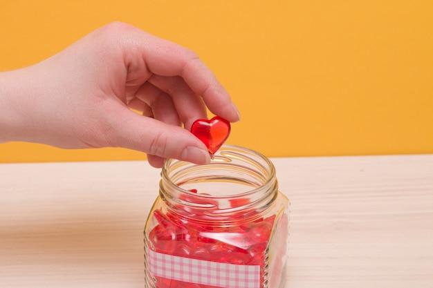 La mano femminile mette un piccolo cuore rosso in un barattolo