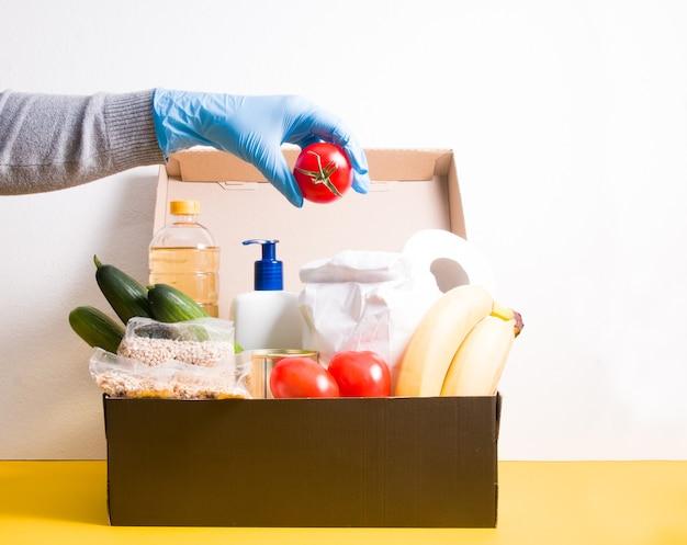 Mano femminile mette un pomodoro in una scatola in generi alimentari, prodotti e prodotti per l'igiene per la donazione, copia spazio, superficie bianca e gialla