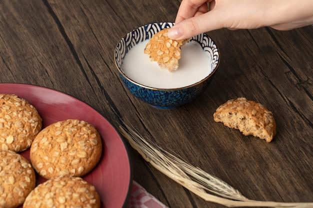 Mano femminile che mette il biscotto della farina d'avena nel latte sulla tavola di legno