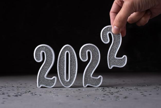 Mano femminile che mette il numero d'argento 2 al 2022 su sfondo scuro, biglietto di auguri, concetto di capodanno, primo piano.