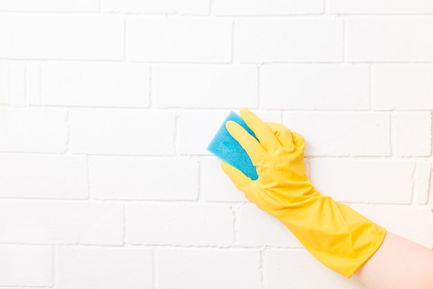 Una mano femminile in un guanto di gomma tiene una spugna paralonne blu per pulire e lavare i piatti