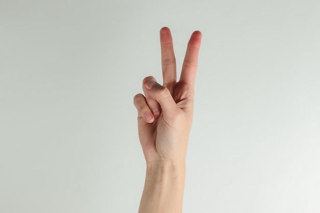 La mano femminile mostra il simbolo di gesto v su una priorità bassa bianca