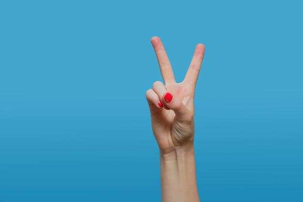 Mano femminile mostra segno di vittoria, lettera v. mano femminile con manicure smalto gel rosso su un tavolo blu. copia spazio