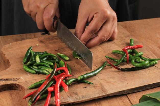 Mano femminile affettare il peperoncino tagliato sul tagliere di legno con coltello