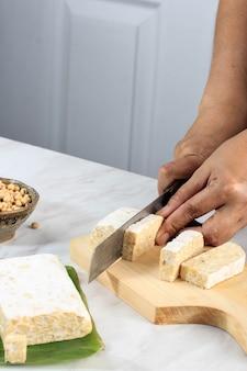 Femmina taglio a mano tempeh o tempe sul tagliere di legno con coltello. tempe è un prodotto di soia fermentata originario dell'indonesia. processo di cottura preparazione del tempeh saltato in padella (orek)