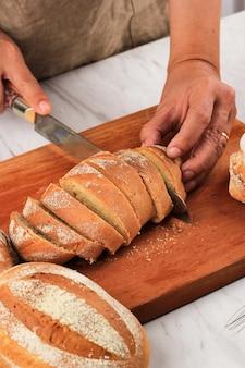Mano femminile che affetta il pane giapponese del focolare del latte facendo uso del coltello del pane per la prima colazione. il pane al latte è il pane giapponese con latte o panna montata, morbido e soffice. messa a fuoco selezionata