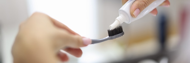 Mano femminile che spreme il dentifricio in pasta dal tubo sul primo piano dello spazzolino da denti. igiene orale quotidiana dopo il concetto di pasti.