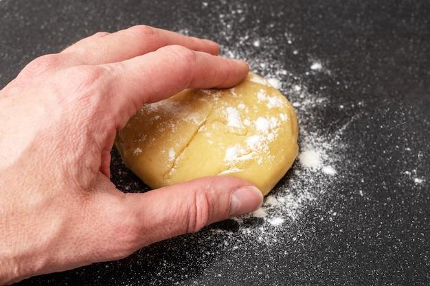Una mano femminile prende un impasto crudo per fare il pane, la torta o la pizza su uno sfondo nero, primo piano, vista dall'alto, copia dello spazio. prodotti da forno fatti in casa