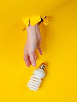La mano femminile prende la lampadina a spirale attraverso carta gialla lacerata. concetto di moda creativa minimalista