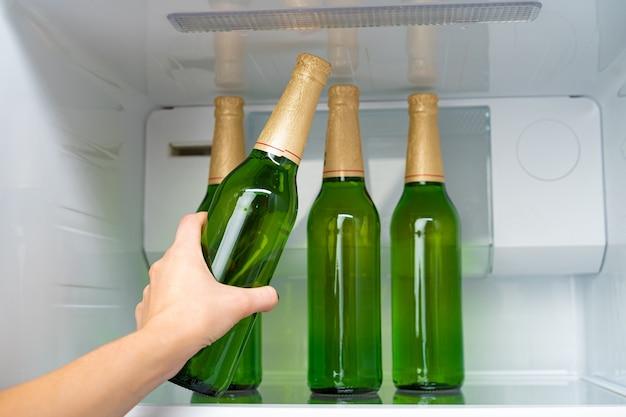 Mano femminile che cattura bottiglia di birra da un frigorifero si chiuda