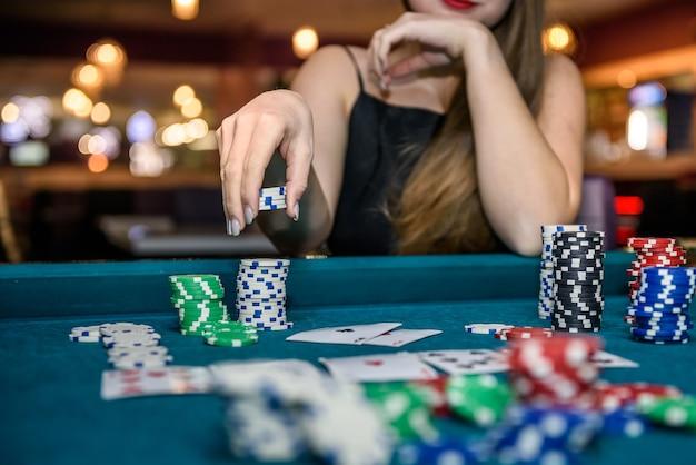Mano femminile che prende le fiches da poker dal mucchio