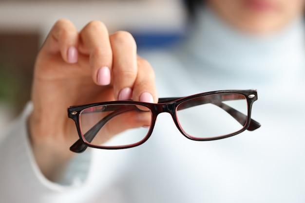 Nella mano femminile ci sono occhiali alla moda alla moda nel concetto di selezione dell'ottica con montature nere