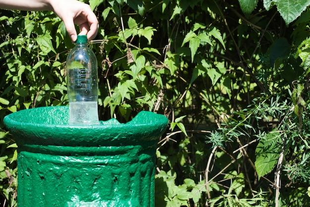 La mano femminile getta una bottiglia di plastica in un piccolo bidone della spazzatura di ferro in un parco verde in estate, da vicino. protezione della natura dalla plastica.