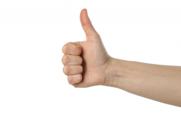 Pollice femminile della mano in su, isolato su superficie bianca