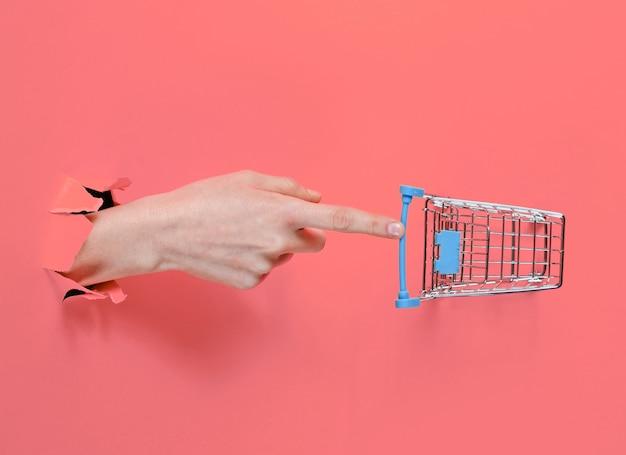 Mano femminile tocca un mini carrello della spesa attraverso carta rosa strappata. concetto di acquisto minimalista