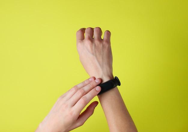 Mano femminile utilizza braccialetto intelligente al polso sul verde