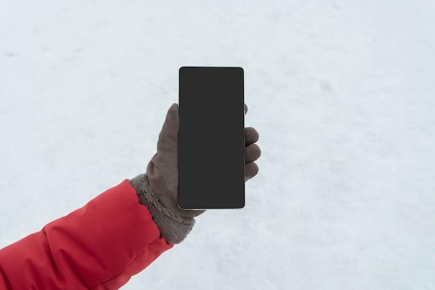 Mano femminile in guanti invernali in possesso di smart phone con schermo vuoto per lo spazio della copia,