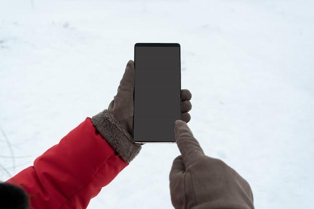 Mano femminile nello smart phone commovente dei guanti di inverno con lo schermo in bianco