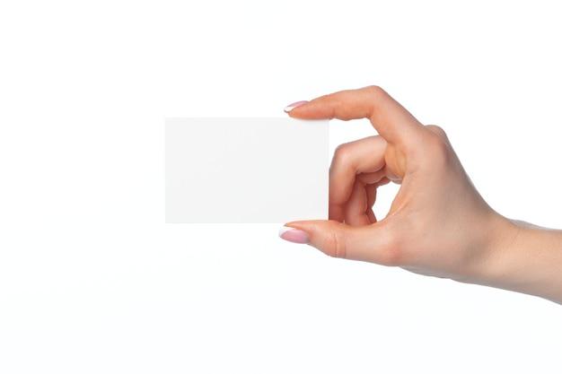 Mano femminile con biglietto da visita bianco vuoto isolato su bianco