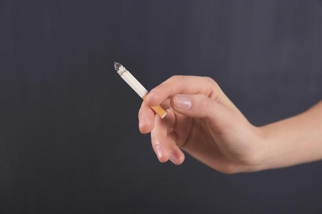 Mano femminile con sigaretta su sfondo scuro