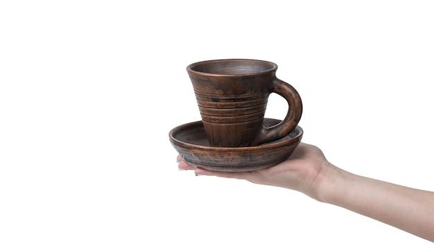 Mano femminile con tazza di argilla e tazza isolata sulla superficie bianca