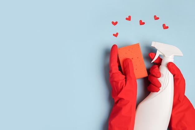 Mano femminile con prodotti per la pulizia e cuori rossi su sfondo blu