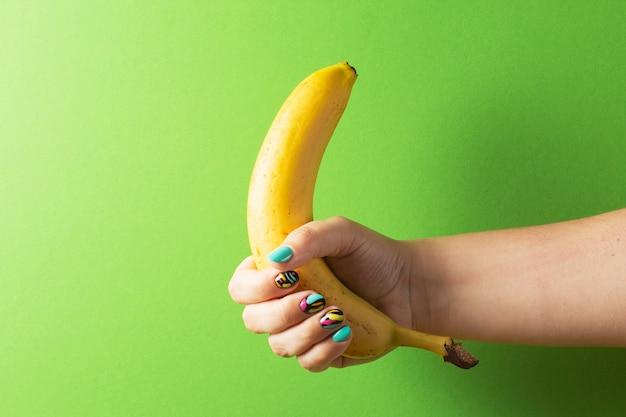 Mano femminile con la banana variopinta della tenuta del manicure su fondo verde