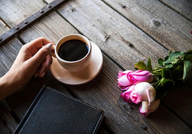 Mano femminile con una tazza di caffè, un libro e fiori su legno.