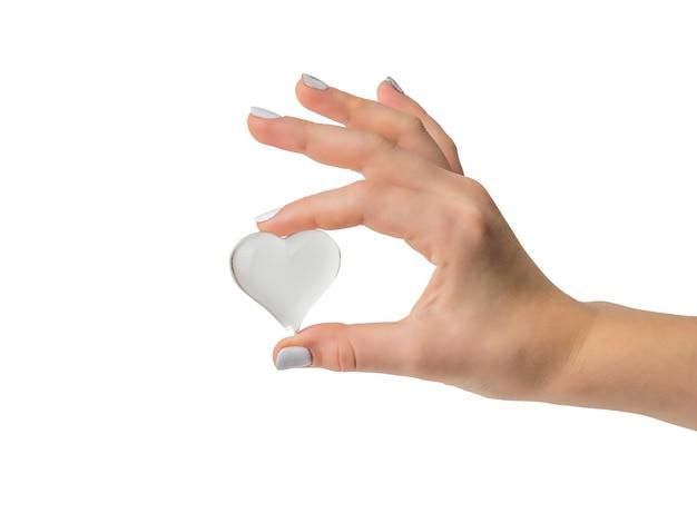 Mano femminile con cuore di vetro isolato