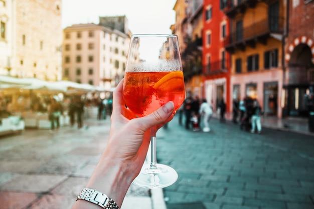 Mano femminile con bicchiere di spritz cocktail alcolico arancione sullo sfondo di vecchi edifici, strada, persone, soleggiata giornata estiva di vacanza a verona, italia.