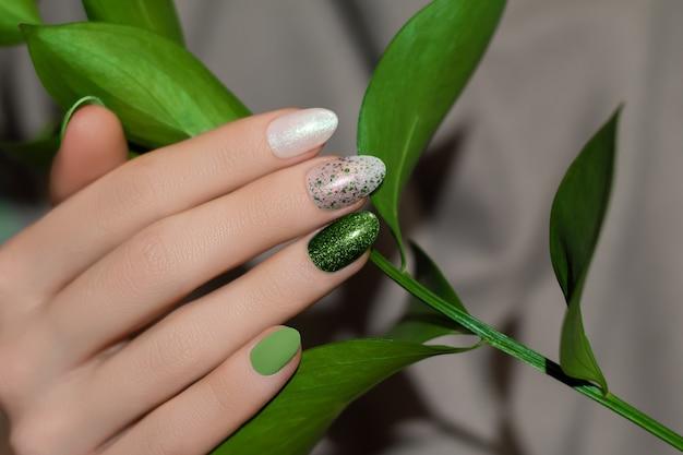 Mano femminile con nail design glitter verde e foglie verdi su tessuto grigio.