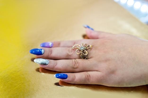 Mano femminile con anello dorato su sfondo dorato