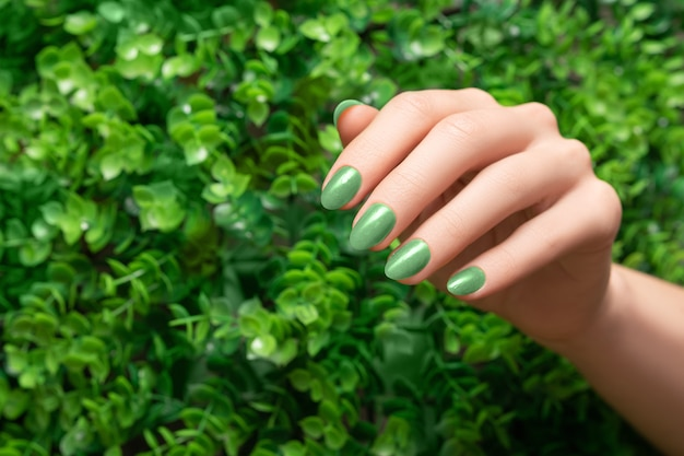 Mano femminile con design delle unghie verde. manicure con smalto verde glitterato. mano della donna sul fondo della natura delle foglie verdi