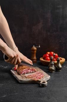 Mano femminile con coltello per affettare la salsiccia di maiale affumicata in budello biologico sul tagliere di legno