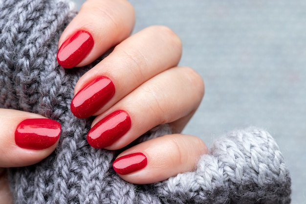 Mano femminile con sciarpa lavorata a maglia con unghie luccicanti rosse