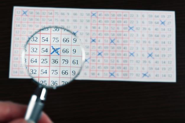 Mano femminile con lente d'ingrandimento analizzando il biglietto della lotteria, primo piano