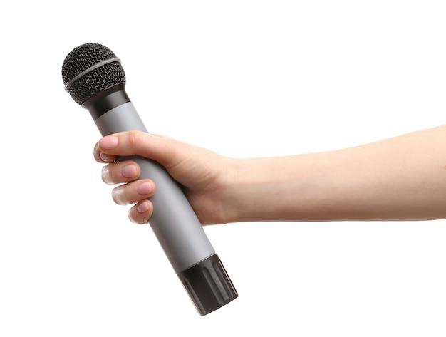 Mano femminile con microfono su bianco