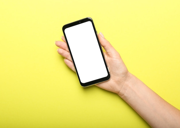 Mano femminile con telefono cellulare su sfondo colorato