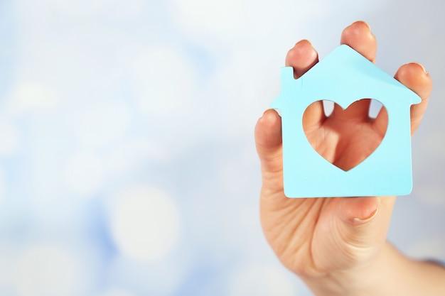 Mano femminile con il modello di casa su sfondo sfocato