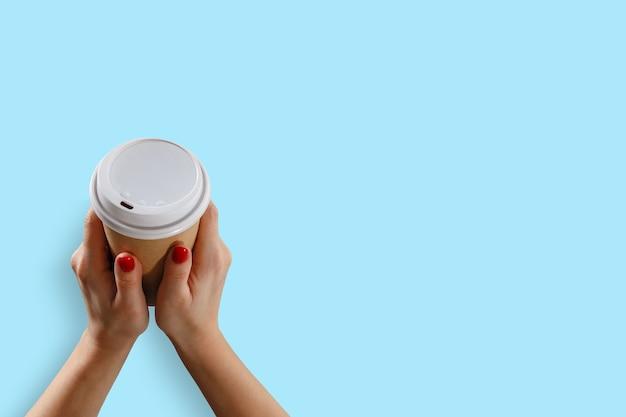 Mano femminile con bicchiere di carta isolato su blue