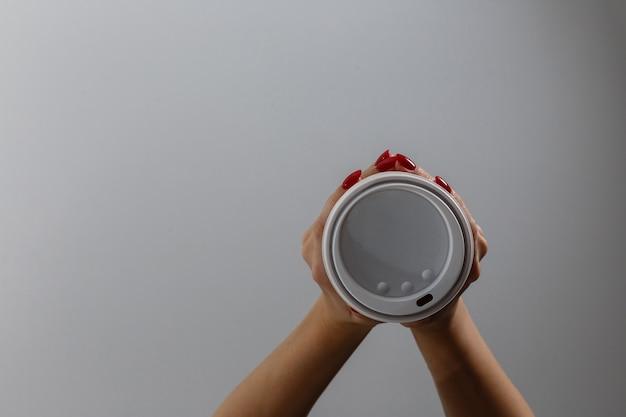 Mano femminile con bicchiere di carta isolato su bianco