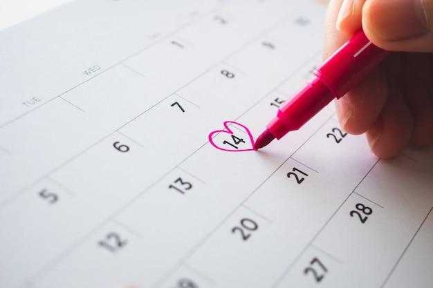Mano femminile con forma di cuore del segno di penna sulla data del calendario al 14 ° giorno di san valentino