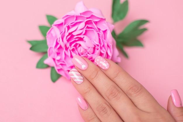 Mano femminile con unghie rosa manicure