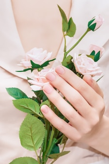 Mano femminile con design delle unghie rosa. mazzo femminile dei fiori della rosa della stretta della mano. mano della donna sul fondo rosa del tessuto.