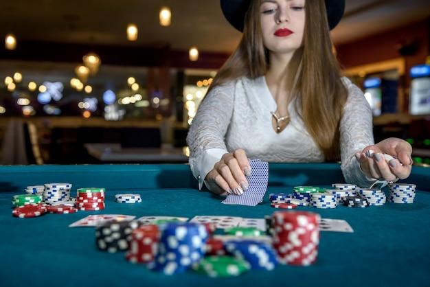 Mano femminile con carte da gioco e fiches da poker da vicino