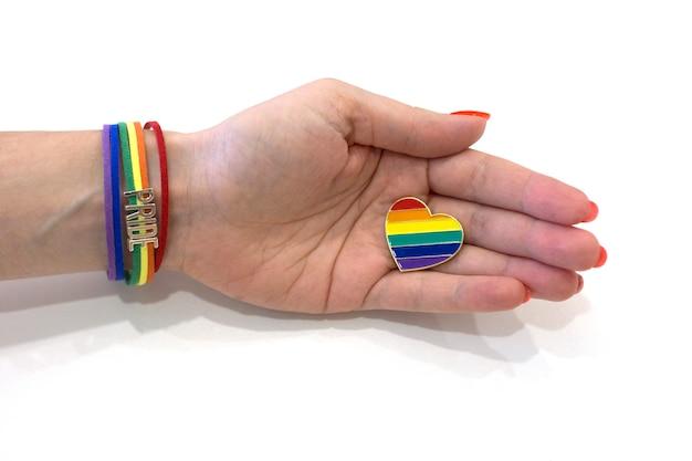 La mano femminile con un braccialetto dell'orgoglio tiene un cuore arcobaleno concetto lgbt icona arcobaleno a forma di cuore