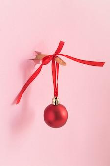 Mano femminile con una palla di natale rossa inserita attraverso una carta rosa strappata foro. avvicinamento. posizione verticale.