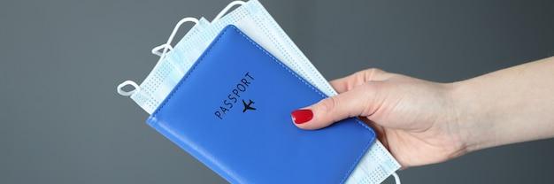Mano femminile con il manicure rosso che tiene il passaporto e il primo piano delle maschere mediche protettive in viaggio