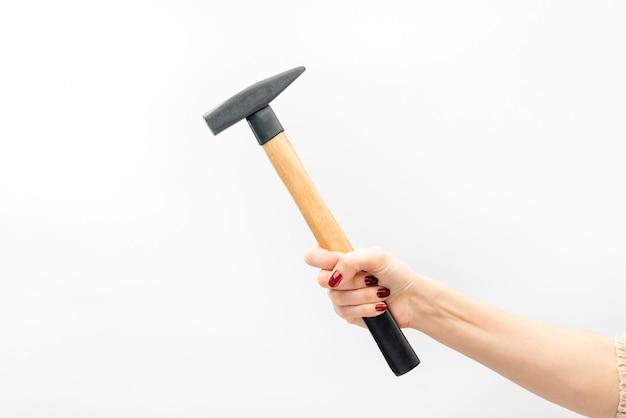 La mano femminile con il manicure rosso tiene il martello isolato sulla parete bianca